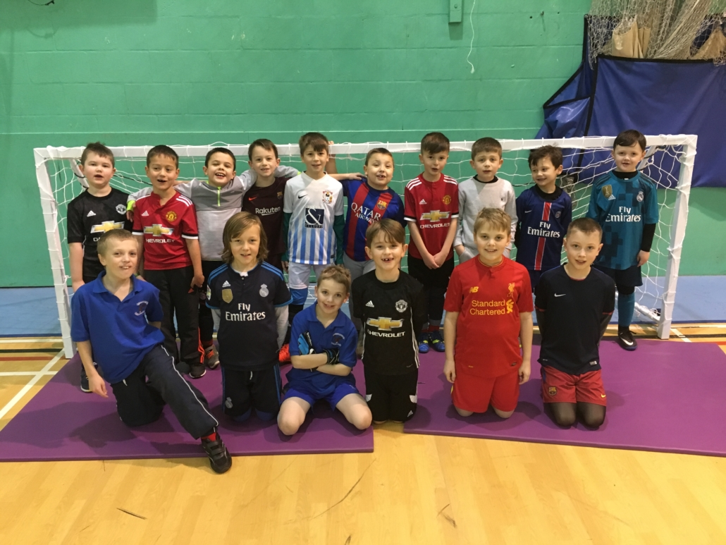 Young group together in goal at indoor mini soccer