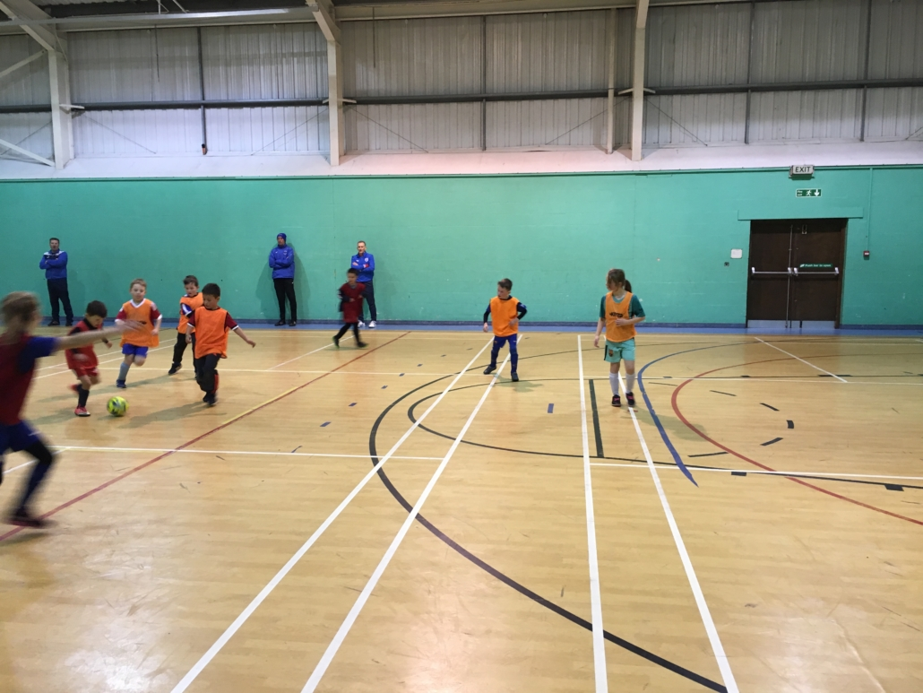 Game action at indoor mini soccer